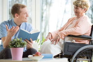 Care assistant reading a book to an elder wheelchair user