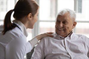 Carer In White Coat Cares For Elderly Man