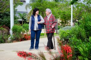 Female Caregiver And Senior Adult Woman Are Walking arm in arm