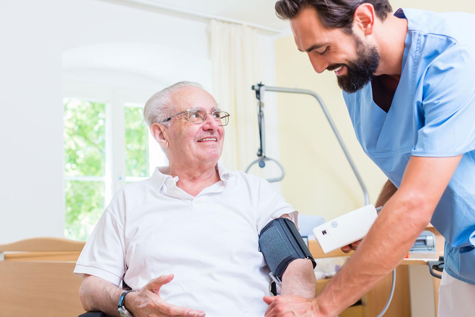 Nurse helps senior man with blood pressure measurement