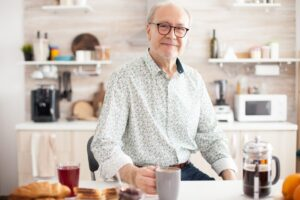 Senior man in kitchen smiling looking at camera holding hot coffee cup.