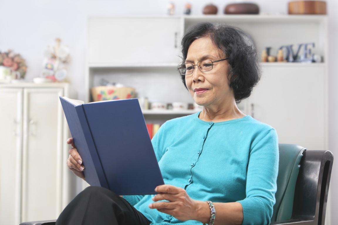 Senior Asian woman reading book at home
