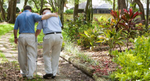 Male carer helps elderly man walking