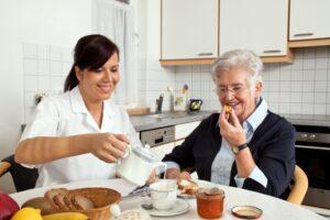 carer helps elderly woman at breakfast